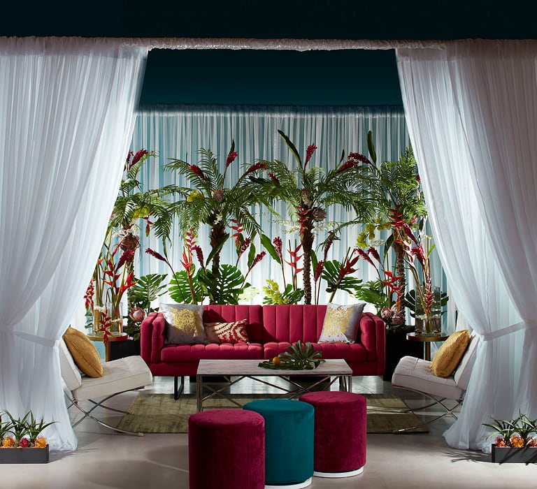 White drape cabana with red sofa and ottomans