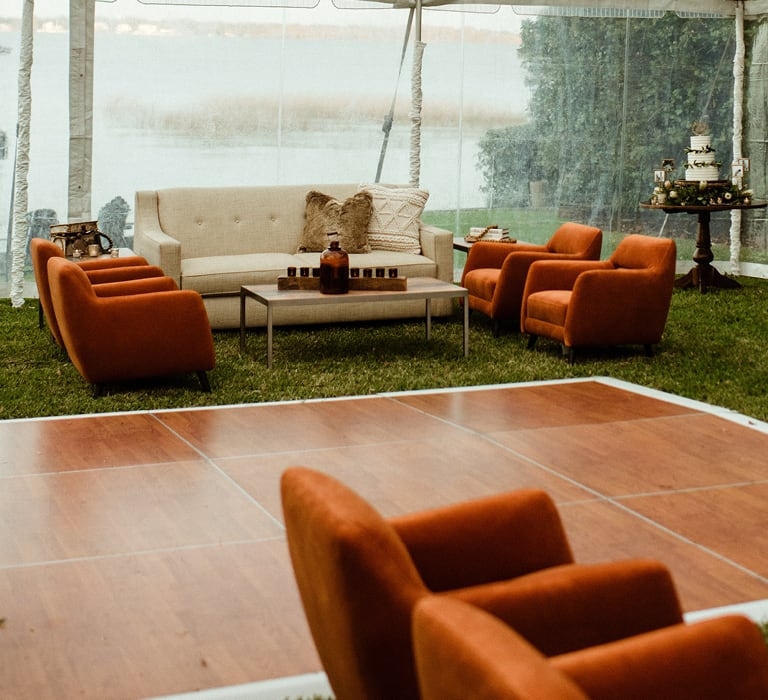 reception in tent with beige and orange furniture