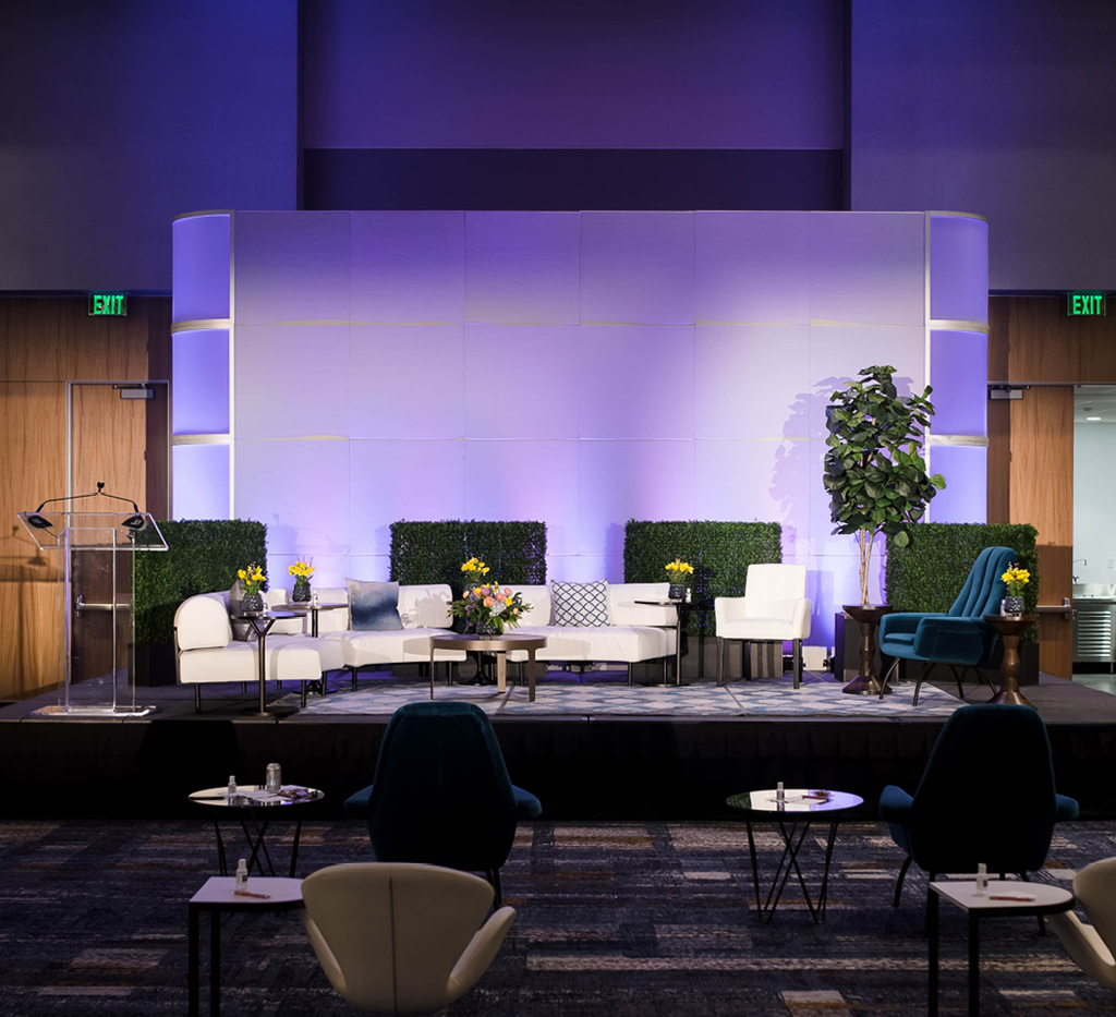 stage set with white and teal rental furnitur