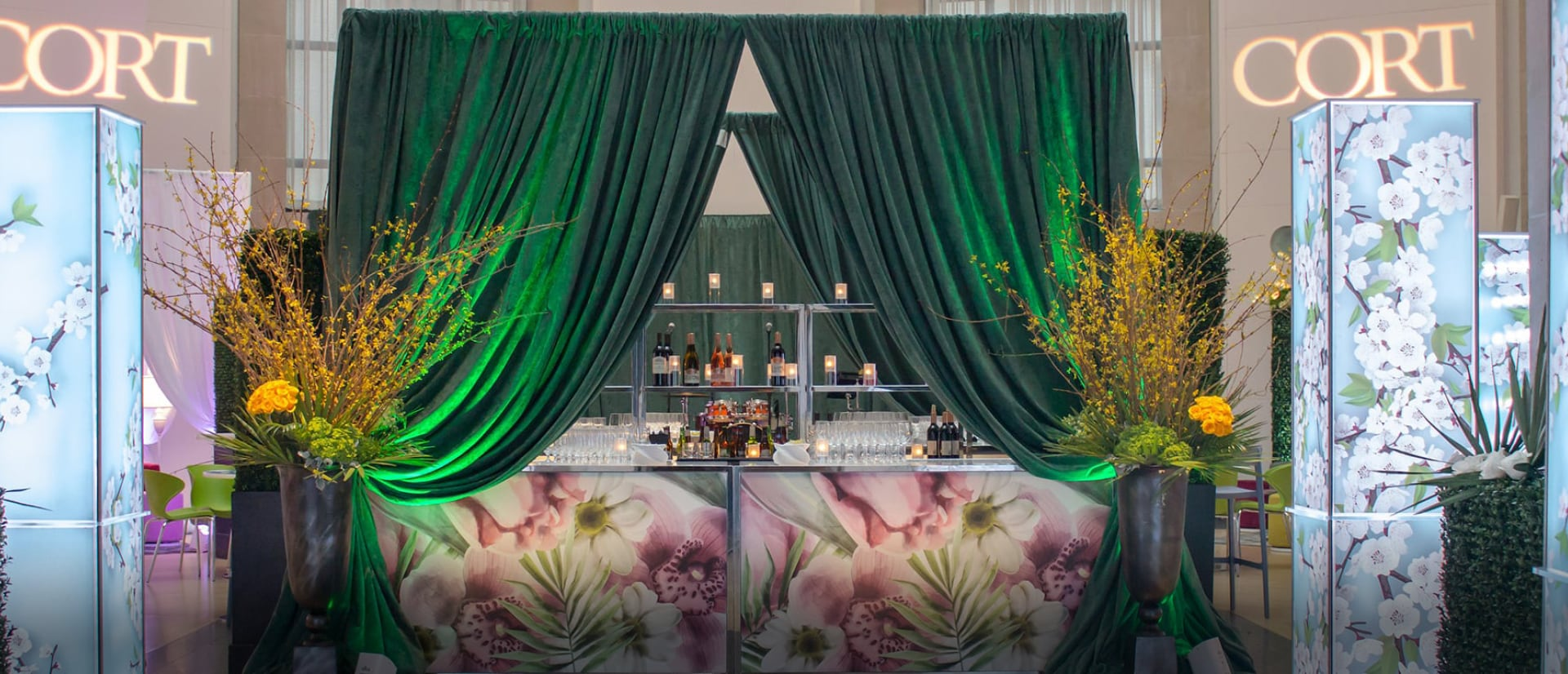 bar area bordered with green drape and lighted columns