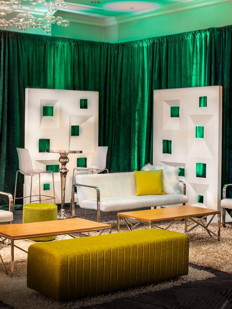 lounge with white furniture and green draped background