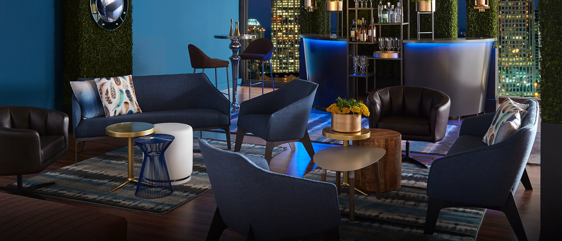 Cocktail reception with blue soft seating and bar with blue light