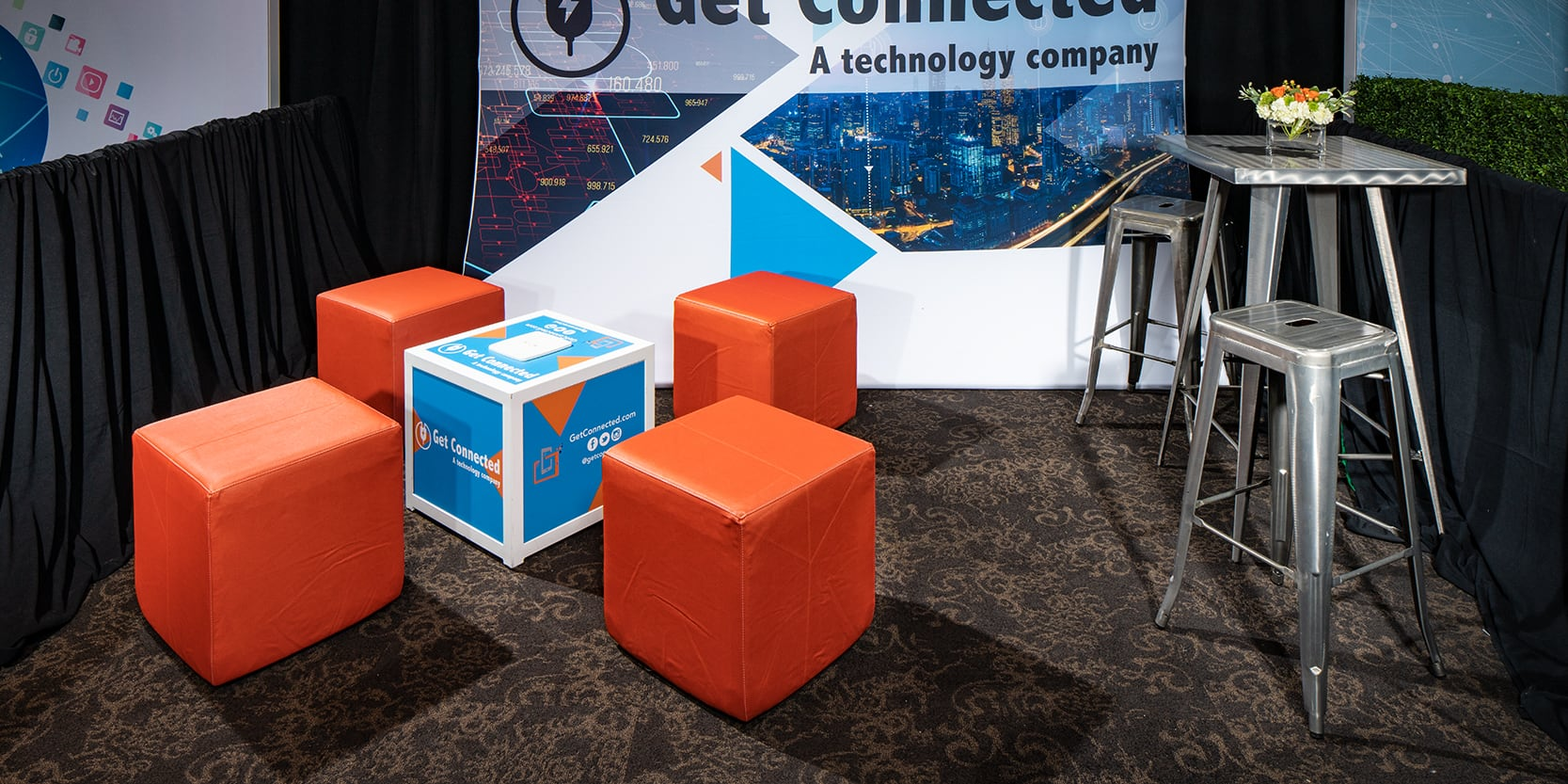 small trade show booth with orange ottomans and silver metallic bar table and barstools