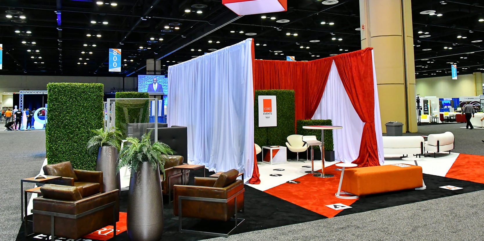 large trade show booth with drape dividers, brown leather seating and orange bench ottomans