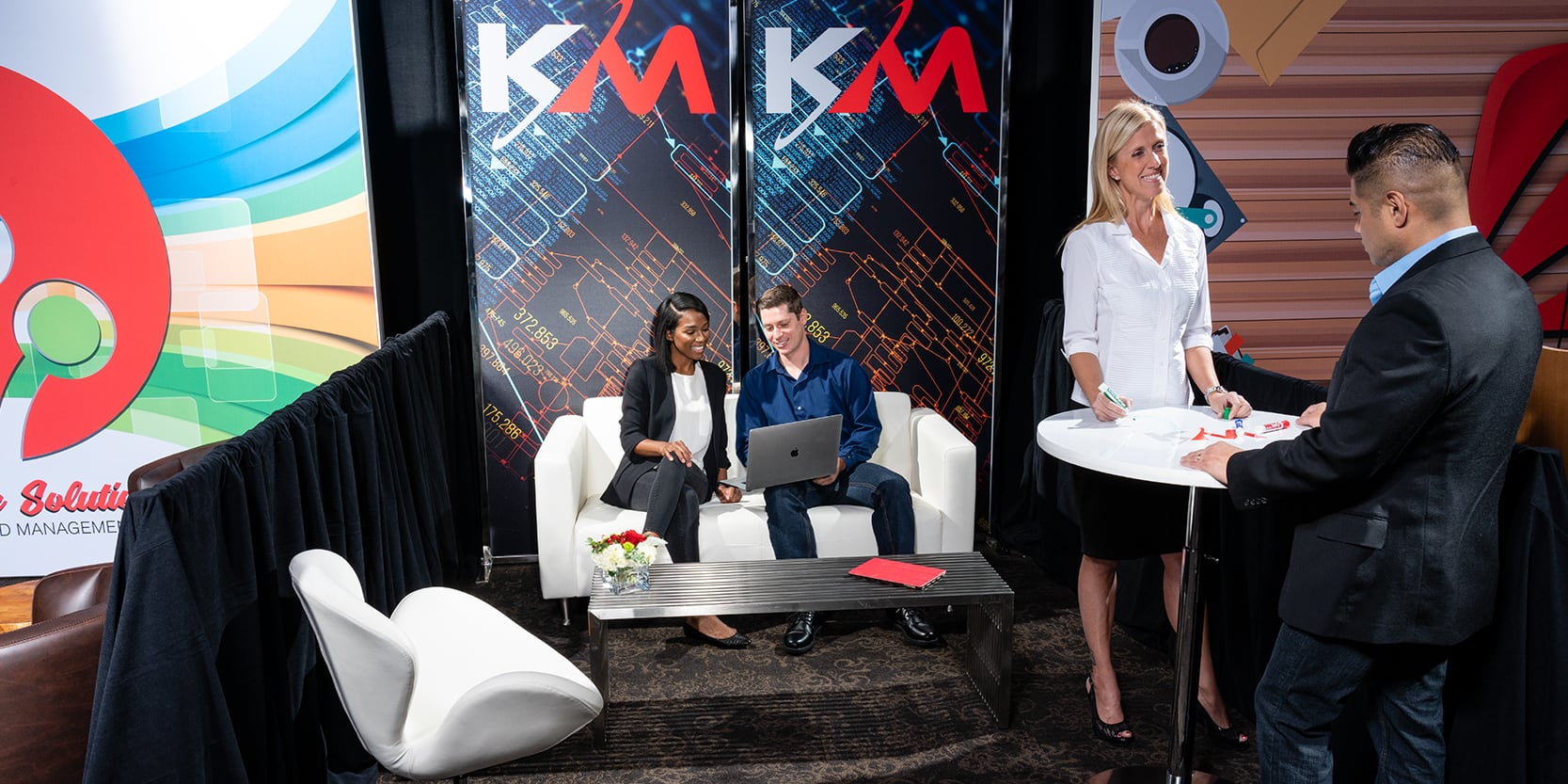 small trade show booth with white furniture rentals and employees talking to clients