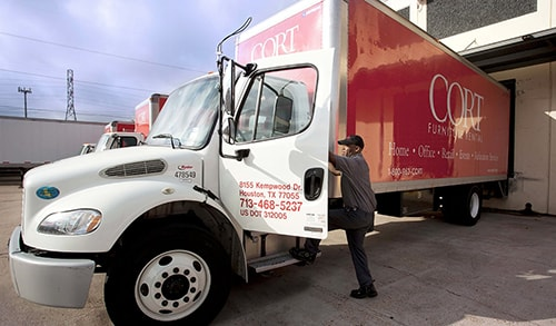 cort driver climbing into a red cort truck to delivery furniture rentals for an event
