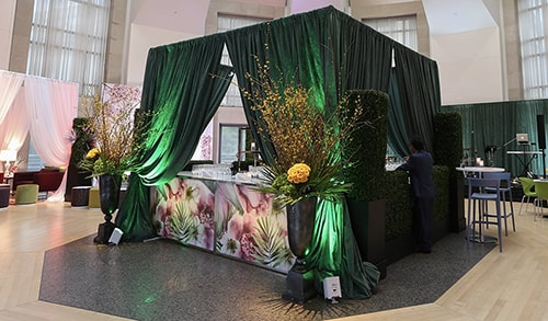cocktail reception event with stylized bar with customized graphic panels surrounded by green drape with uplighting