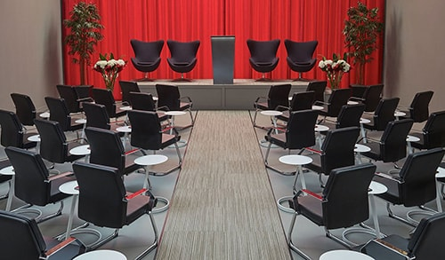 meeting with rows of black guest chairs, accent chairs with a lectern on stage and red drape backdrop